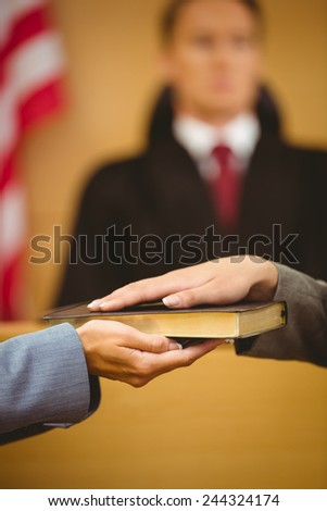 Witness swearing on the bible telling the truth in the court room - stock photo