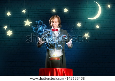wizard casts a spell over his hat from the hat off smoke, colored lights and magic butterfly - stock photo