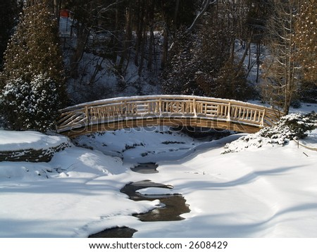 woden bridge on a frozen river - stock photo
