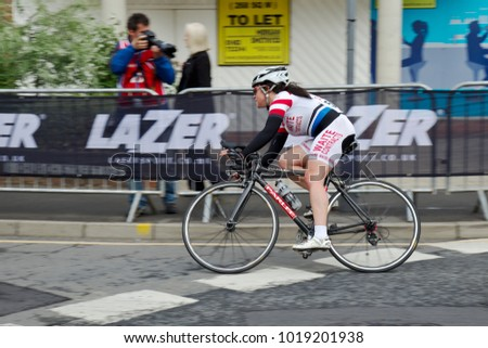 WOKING, UK - JUNE 11: A lone female rider competing for the Johnson Paint Cycling Trophy takes the final tight hairpin bend before heading toward the finish line on June 11, 2013 in Woking