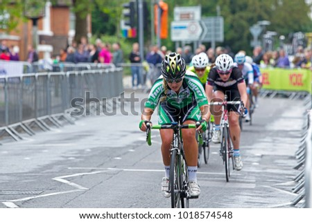WOKING, UK - JUNE 11: AN unnamed rider leading one of the chasing packs heads down a long straight section at speed during the Pearl Izumi Halfords road race on June 11, 2013 in Woking.