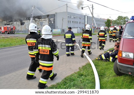 WOLKA KOSOWSKA, POLAND - MAY 10, 2011: Firefighters going to extinguish the fire in a China Mart storehouse. The fire burned 150 storage units covering nearly 2 hectares. - stock photo