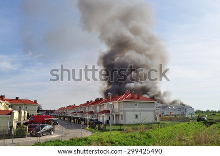 WOLKA KOSOWSKA, POLAND - MAY 10, 2011: Smoke rising from a raging fire in a China Mart storehouse - view from the housing estate. The fire burned 150 storage units covering nearly 2 hectares. - stock photo