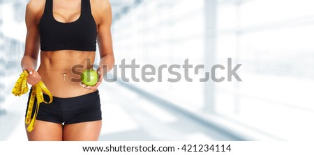 Woman abdomen with measuring tape and apple. - stock photo