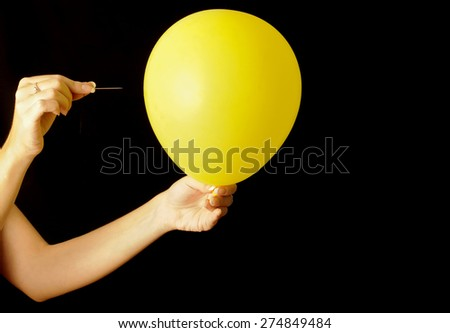 Woman about to pierce a balloon with a needle - stock photo