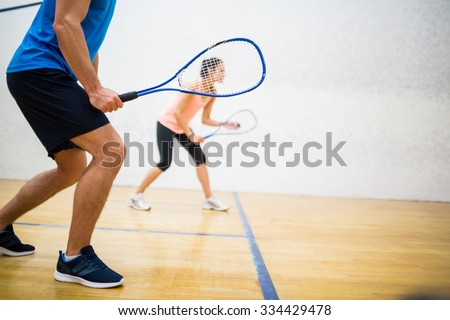Woman about to serve the ball in the squash court - stock photo