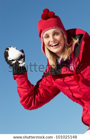 Woman About To Throw Snowball Wearing Warm Clothes On Ski Holiday In Mountains - stock photo