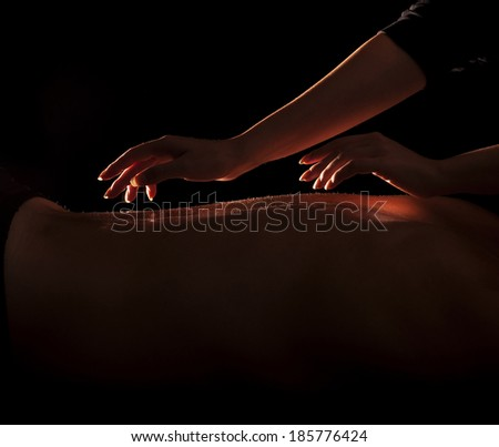 Woman about to touch a man's back, back massage