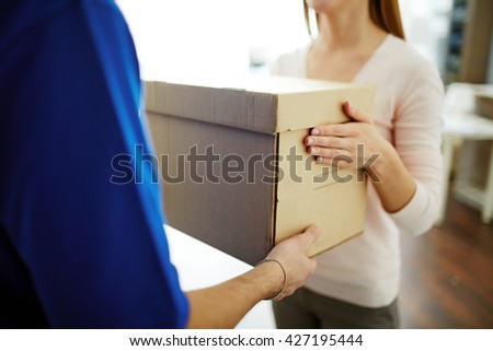 Woman accepting a box from delivery man - stock photo