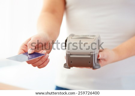 Woman accepts credit card to pay, in the store - stock photo