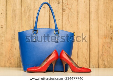 Woman accessories on wood background, blue handbag and red stileto - stock photo