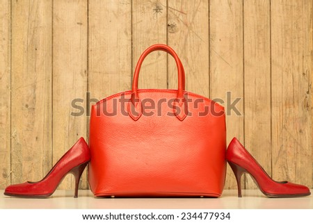 Woman accessories on wood background, red handbag and stileto