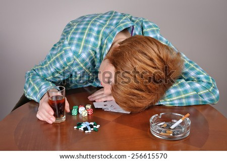 Woman addicted to vice. Exhausted  woman with her head on the table sleeping next to cards, dice, pills and ashtray with cigarette holding a glass of alcohol  - stock photo