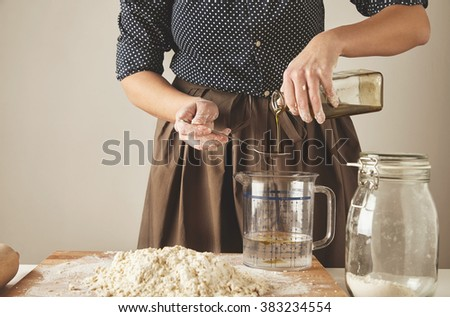Woman adds some olive oil in water in measure cup behind the table with dough ingredients, for making pasta or dumplings Cooking presentation process - stock photo