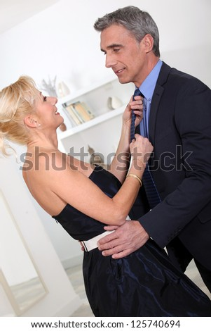 Woman adjusting husband's tie - stock photo