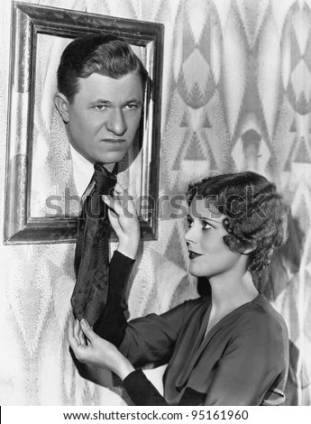 Woman adjusting tie of man in picture frame - stock photo