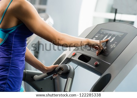 woman adjusts the treadmill at the beginning of training, do fitness in the sport club - stock photo