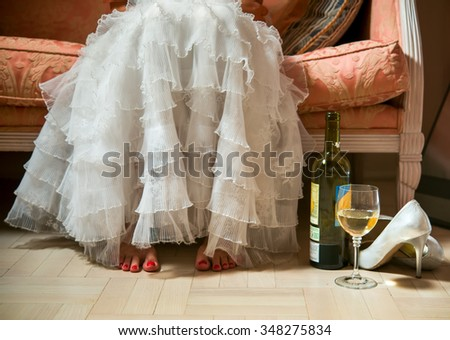 woman after a party and wedding in a luxurious white dress with ruffles. He sits on the couch next to a bottle of wine and standing glass - stock photo