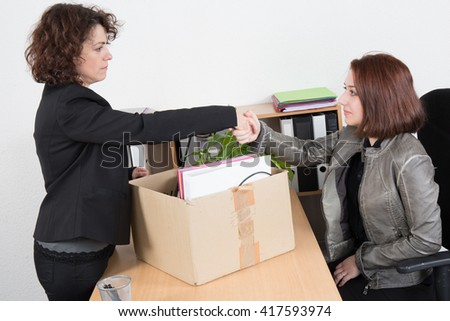 Woman after fired shake hand of her boss - stock photo