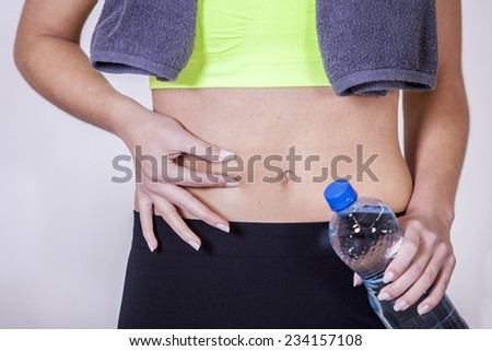 Woman after fitness training, pinches fat on the belly - stock photo