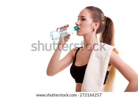 Woman after sport drinking water from bottle with towel on shoulder isolated over white background