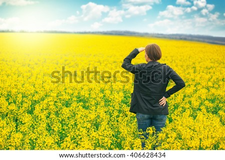 Woman agronomist standing in the field of blooming cultivated rapeseed, female agricultural expert controlling the growth of crops and looking to distant point on the horizon.
