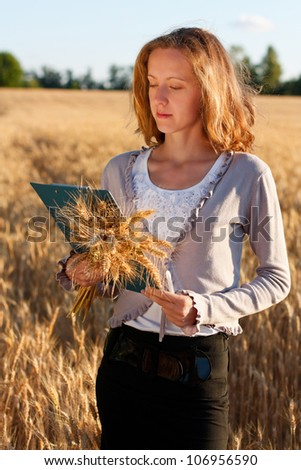 Woman agronomist with document in hand analyzing wheat ears against a background of wheat field - stock photo