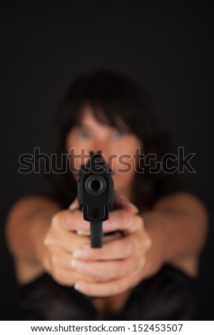 Woman aiming a gun against a dark background. With focus on the gun