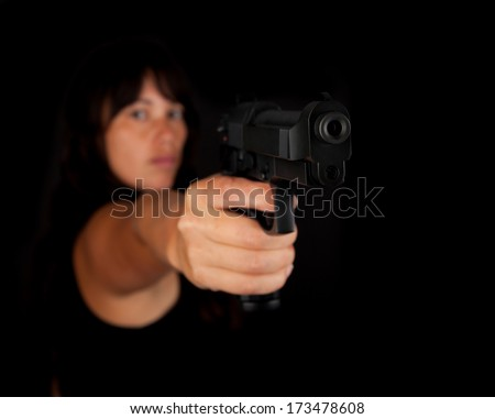 Woman aiming a gun against a dark background. With focus on the gun - stock photo