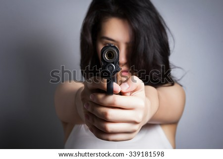 Woman aiming a gun,focus on the gun.  - stock photo