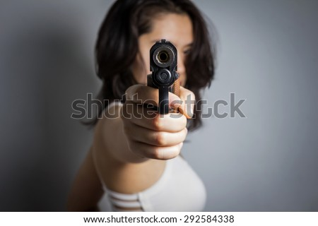 Woman aiming a gun isolated on black background. With focus on the gun.