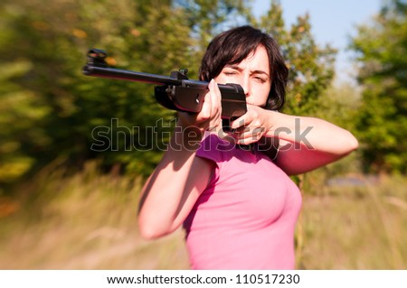 Woman aiming rifle in the sunny summer forest. Lensbaby effect - stock photo