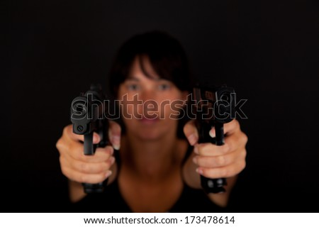 Woman aiming two guns against a dark background. With focus on the guns