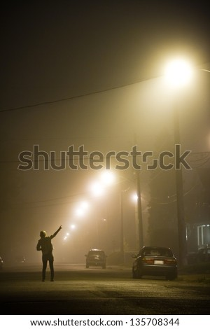 Woman alone in the middle of the foggy street pointing at something - stock photo