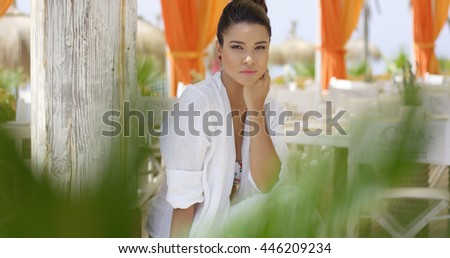 Woman alone outdoors with plant in foreground - stock photo