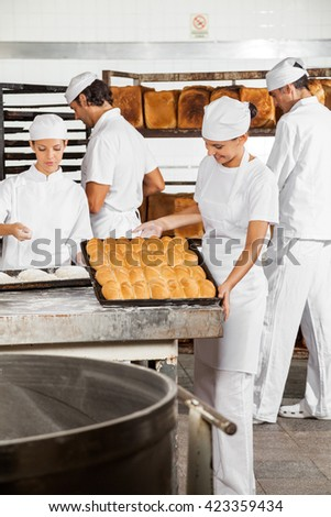 Woman Analyzing Breads While Colleagues Working In Bakery