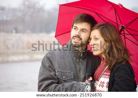 Woman and a bearded man under a red umbrella on a rainy day, outdoors,