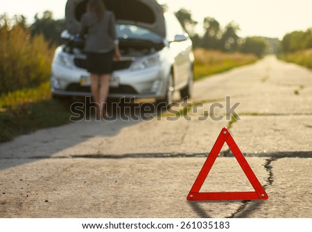woman and a broken car