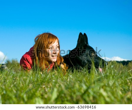 woman and a dog lying on the grass