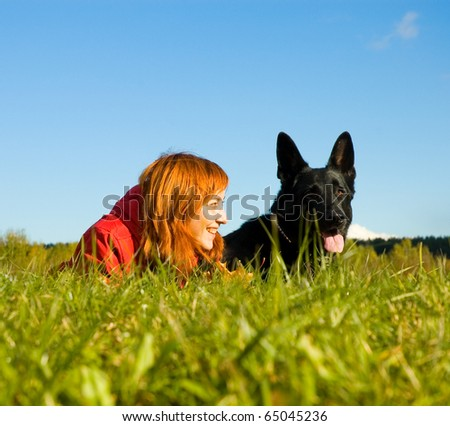 woman and a dog lying on the grass - stock photo