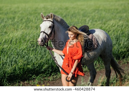 Woman and a horse walking in the field