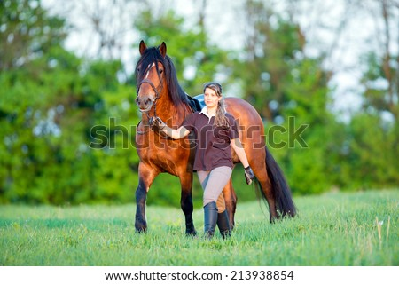 Woman and a horse walking in the field at sunset