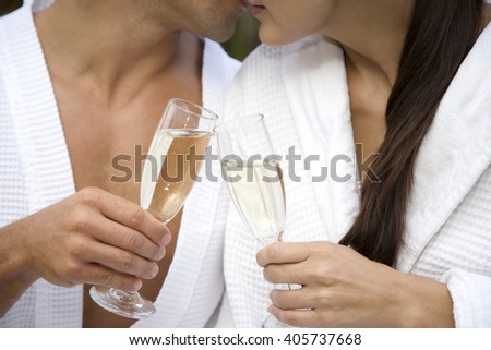 Woman and a man celebrating with champagne and being affectionate - stock photo