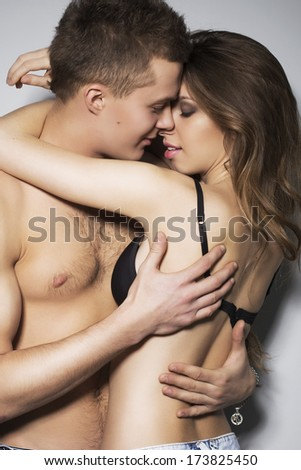 Woman and a man holding each other in sexy pose with lust in their eyes - stock photo