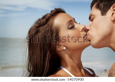 Woman and a man kissing at a beach - stock photo