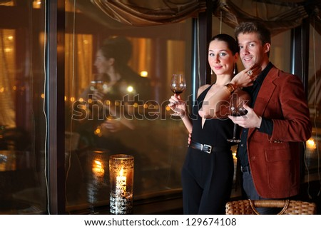 woman and a man with a glass of wine at the restaurant - stock photo
