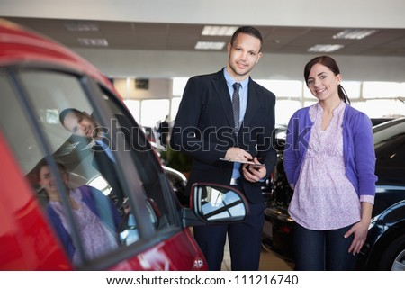 Woman and a salesman standing side by side in a car shop - stock photo
