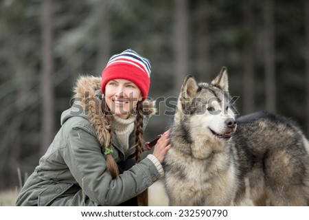 Woman and Alaskan Malamute walk in autumn dark forest. focus on dog, daylight - stock photo