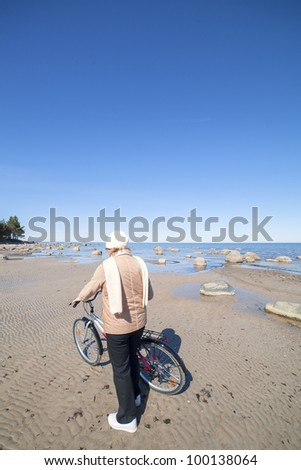 Woman and bicycle at sea.