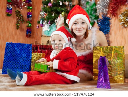 Woman and boy dressed like Santa Claus with Christmas gifts - stock photo